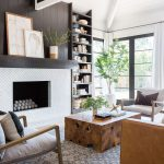 Living Room, Patterned Rug, Black Wooden Accent Wall, White Fireplace, Wooden Square Coffee Table, White Chairs, Brown Sofa, Built In Shelves, Vaulted Ceiling