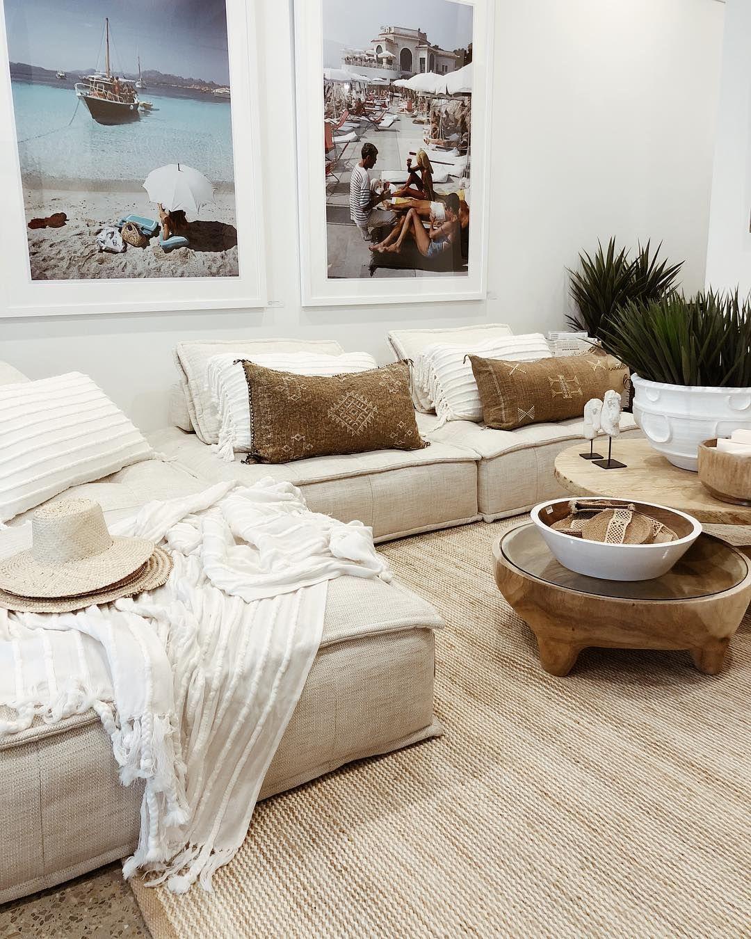 living room, rattan rug, white corner sofa, wooden round table, white pots