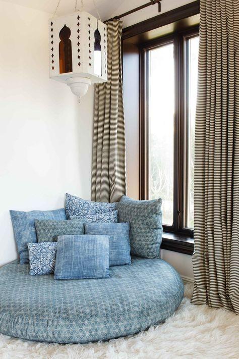 living room, white rug floor, white wall, blue floor round ottoman, blue pillows