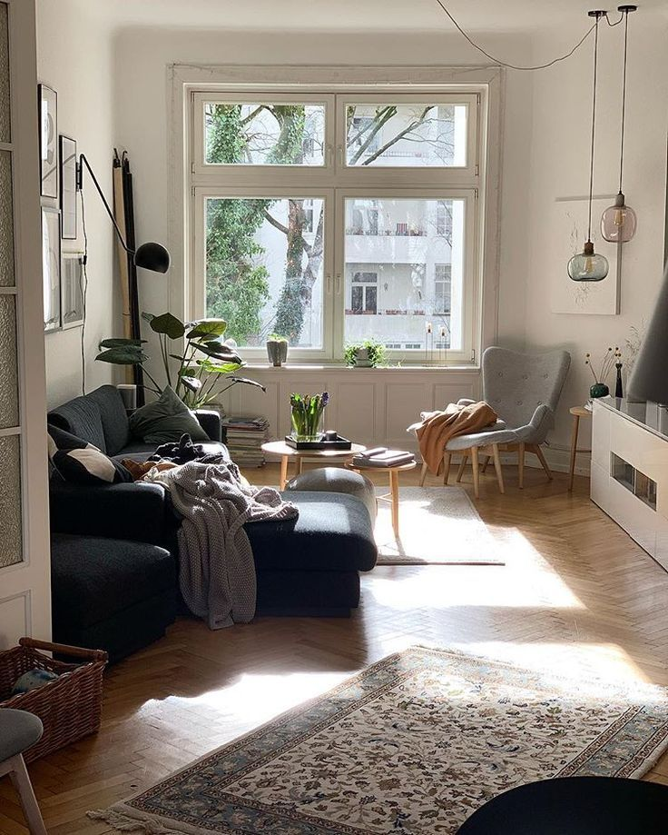 living room, wooden chevron floor, white wall, white cabinet, grey chair, dark grey sofa, glass pendants, black sconce, round coffee table
