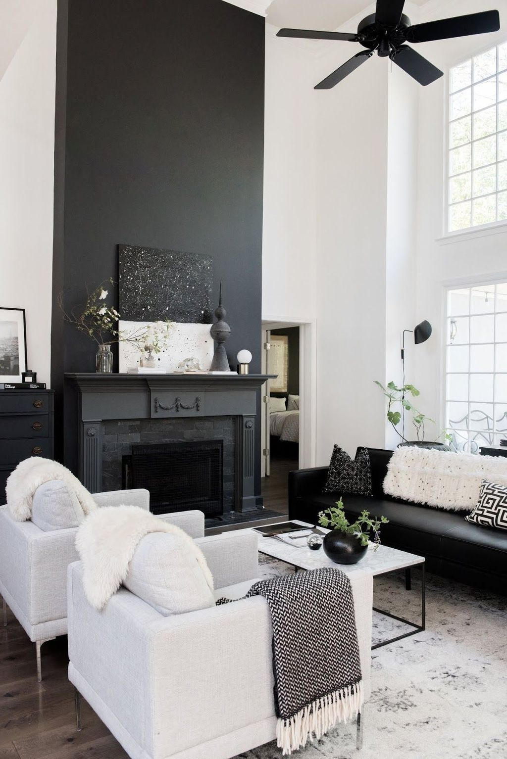 living room, wooden floor, black accent wall, black fireplace, black sofa, white chairs, white marble coffee table, white wall, white patterned rug