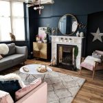 Living Room, Wooden Floor, Black Wall, Grey Sofa, Pink Sofa, Pink Chair, Round Mirror, White Fireplace, White Coffee Table, White Fur Rug, Chandelier