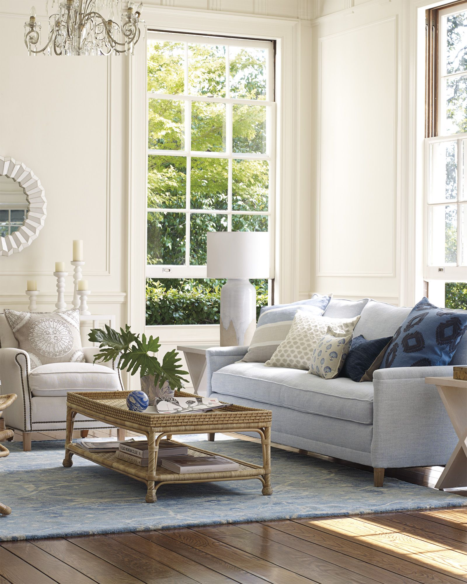 living room, wooden floor, blue rug, light blue sofa, white chair, wooden tray coffee table, side table, white wall, white table lamp