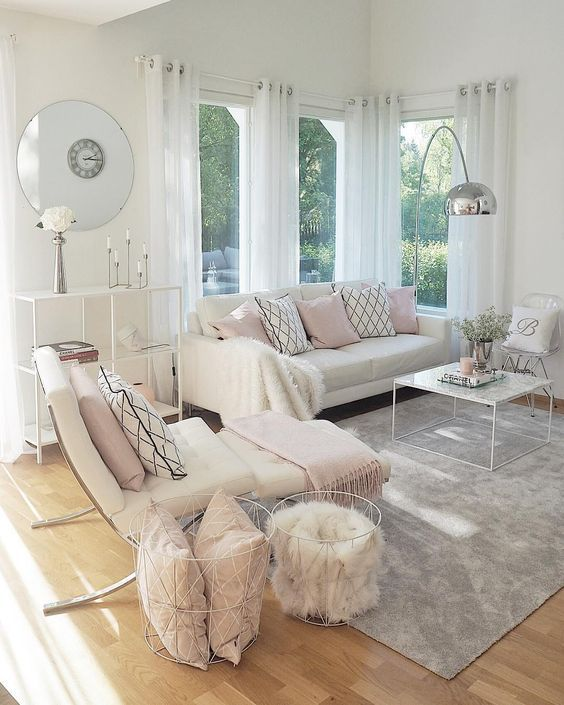 living room, wooden floor, grey rug, white wall, white sofa, white lounge chair, white ottoman, white marble coffee tbale, silver floor lamp, whtie shelves