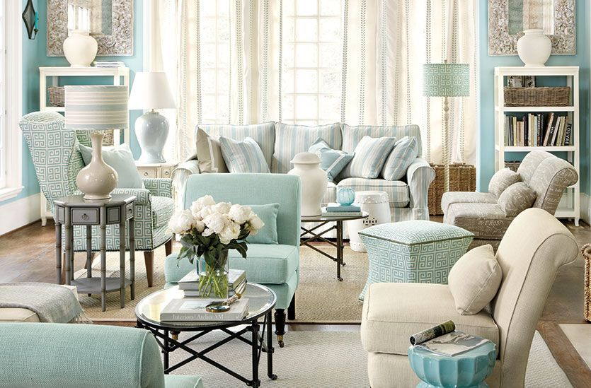 living room, wooden floor, light blue sofas and chairs, blue floor lamp, white table lamp, side table, blue wall