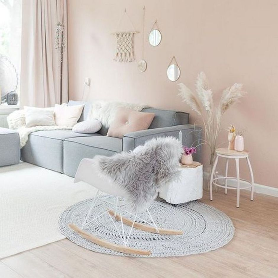 living room, wooden floor, pink wall, grey sofa, whtie rocking chair, white rug, grey woven round rug