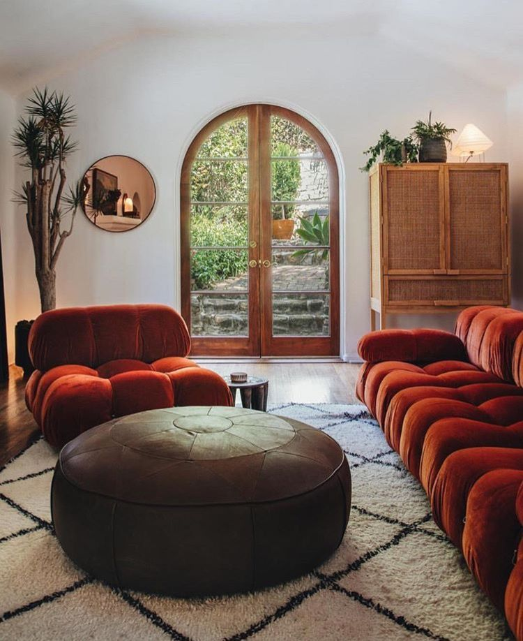 living room, wooden floor, red velvet sofa and chair, brown leather ottoman for coffee table, white wall, vaulted ceiling, rattan cabinet, round mirror, glass door