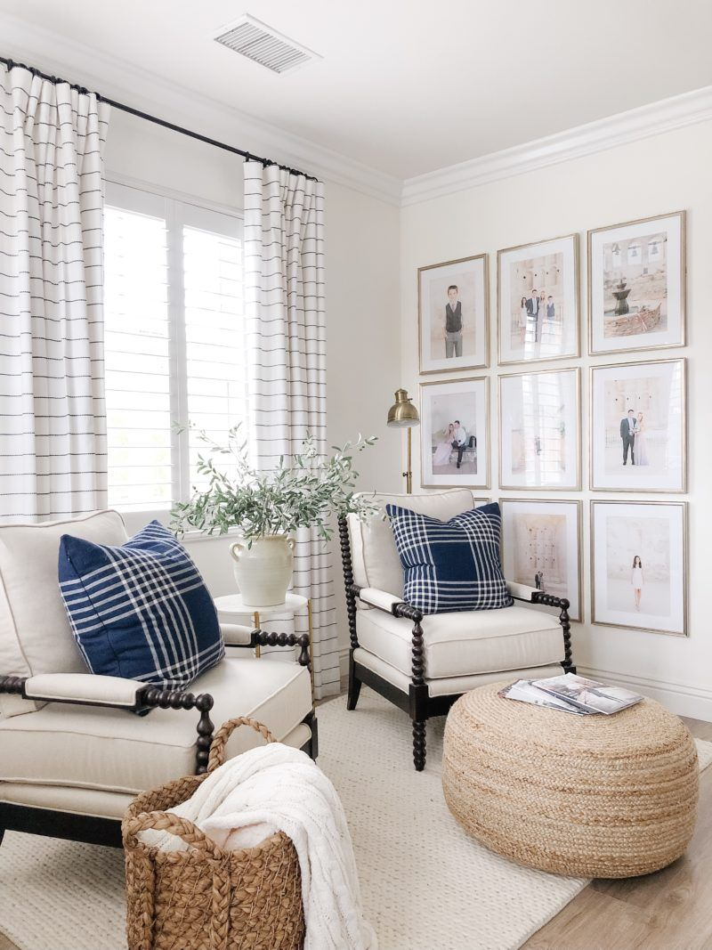living room, wooden floor, white rug, white chairs, rattan round ottoman, rattan basket, white side table, golden floor lamp, striped curtain