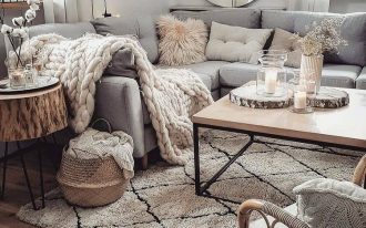 living room, wooden floor, white rug, white wall, grey corner rug, wooden coffee tbale, wooden side table, rattan chair, round mirror