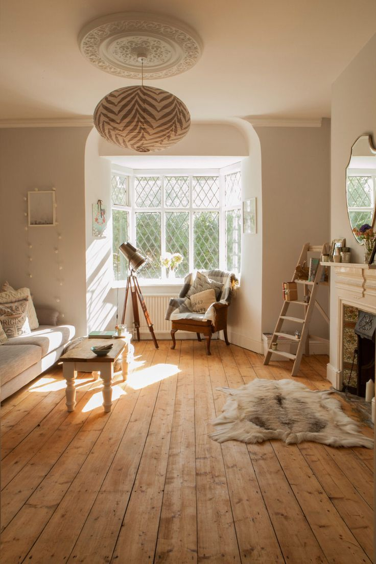 living room, wooden floor, white sofa, white window bay, white fireplace, chair, wooden rack stairs