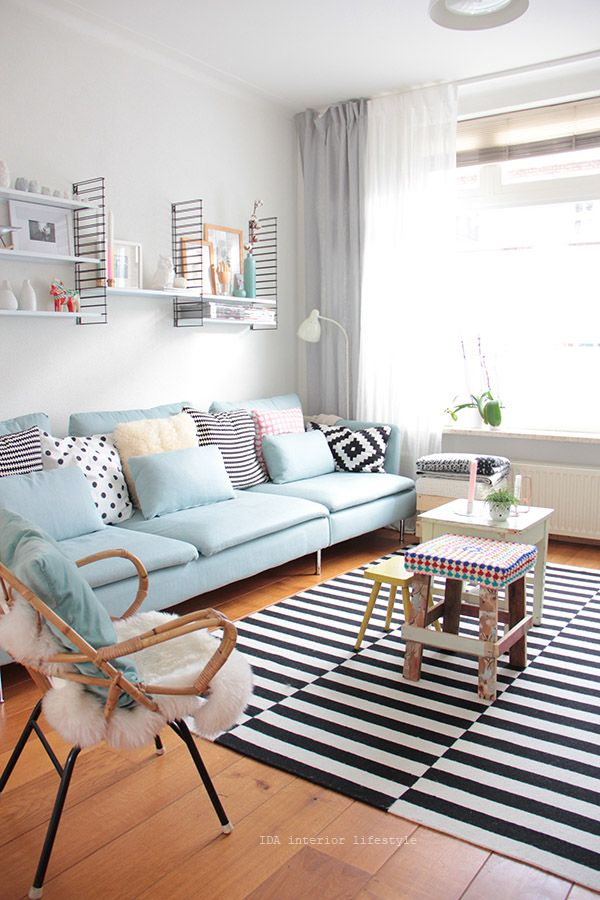 living room, wooden floor, white wall, blue sofa, rattan chair, pillows, floating shelves