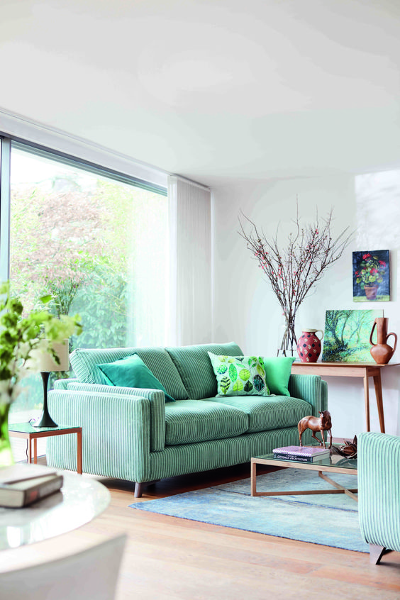 living room, wooden floor, white wall, green striped sofa and chairs, low coffee table, wooden console table, lamp
