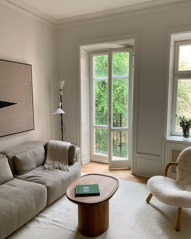 living room, wooden floor, white wall, grey sofa, white chair, grey rug, round tray coffee table, white floor lamp
