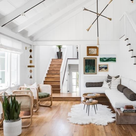 living room, wooden floor, white wall, rattan chairs, wooden corner bench, wooden tray coffee table, vaulted ceiling, lined fixture