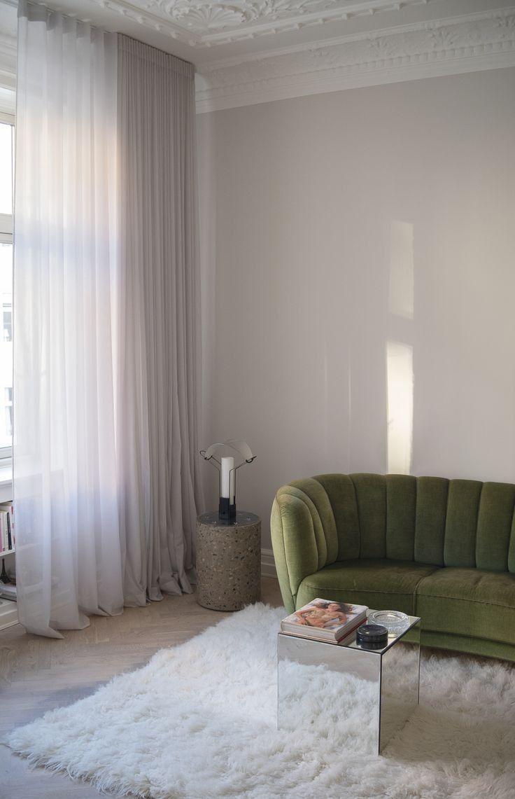living room, wooden floor, white wall, white rug, green velvet sofa, white curtain, white shelves