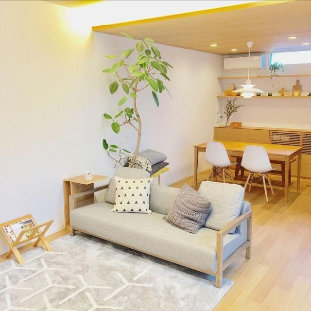 living room, wooden floor, white wall, wooden ceiling, wooden dining table, white midcentury chair, wooden sofa with grey cushion