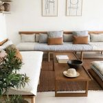 Living Room, Wooden Sofa With Cushion, Pillows, Wooden Coffee Table, White Wall, Rattan Rug, Floating Shelves