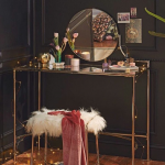 Make Up Station, Wooden Floor, Black Wall, Wainscoting, Golden Table With Glass Top, Golden Stool With White Fur, Round Mirror
