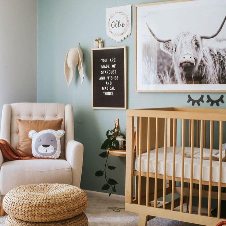 nursery, concrete floor, green wall, grey wall, white chair, rattan ottoman, wooden crib