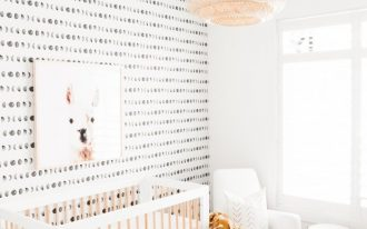 nursery, white wall, accent wal, white wooden crib, cream rug, rattan pendant, rattan ottoman