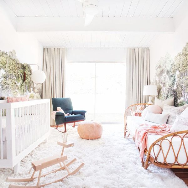 nursery, wooden floor, white rug, white wall, trees wallpaper, rattan sofa bed, white wooden crib, black chair, ottoman