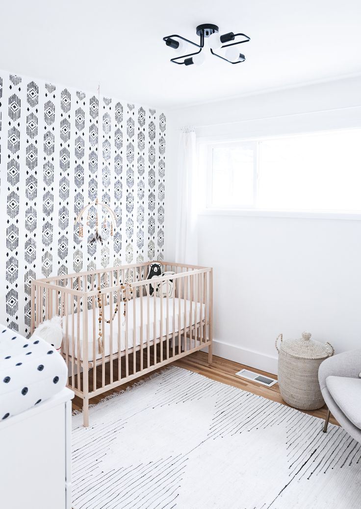 nursery, wooden floor, white wall, patterned wall, wooden crib, grey chair, white diaper change