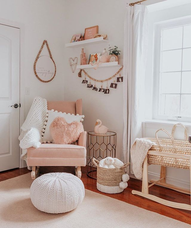 nursery, wooden floor, white wall, white floating shelves, pink rocking chair, white woven ottoman, rattan crib