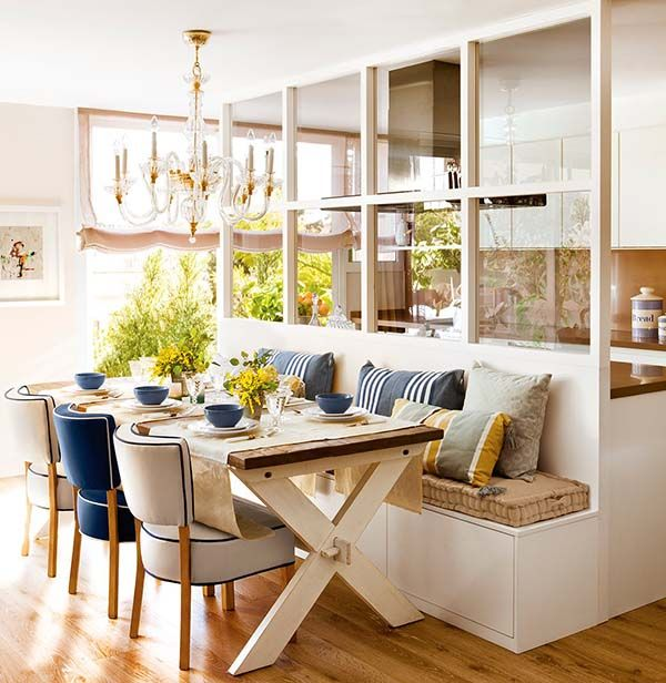 open kitchen, white built in dining bench, blue chairs, wooden dining table, chandelier, glass partition