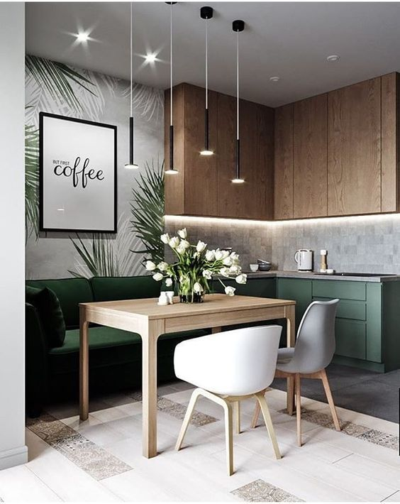 open kitchen, wooden top cabinet, grey backsplash, green bottom cabinet, green sofa, wooden table, white chairs, pendant