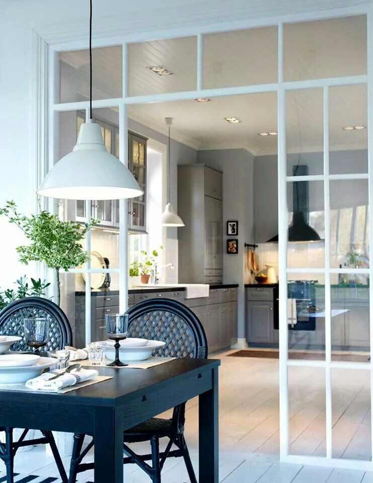 open room, white wooden floor, white wall, white pendant, black dining table, black chairs, grey kitchen cabinet