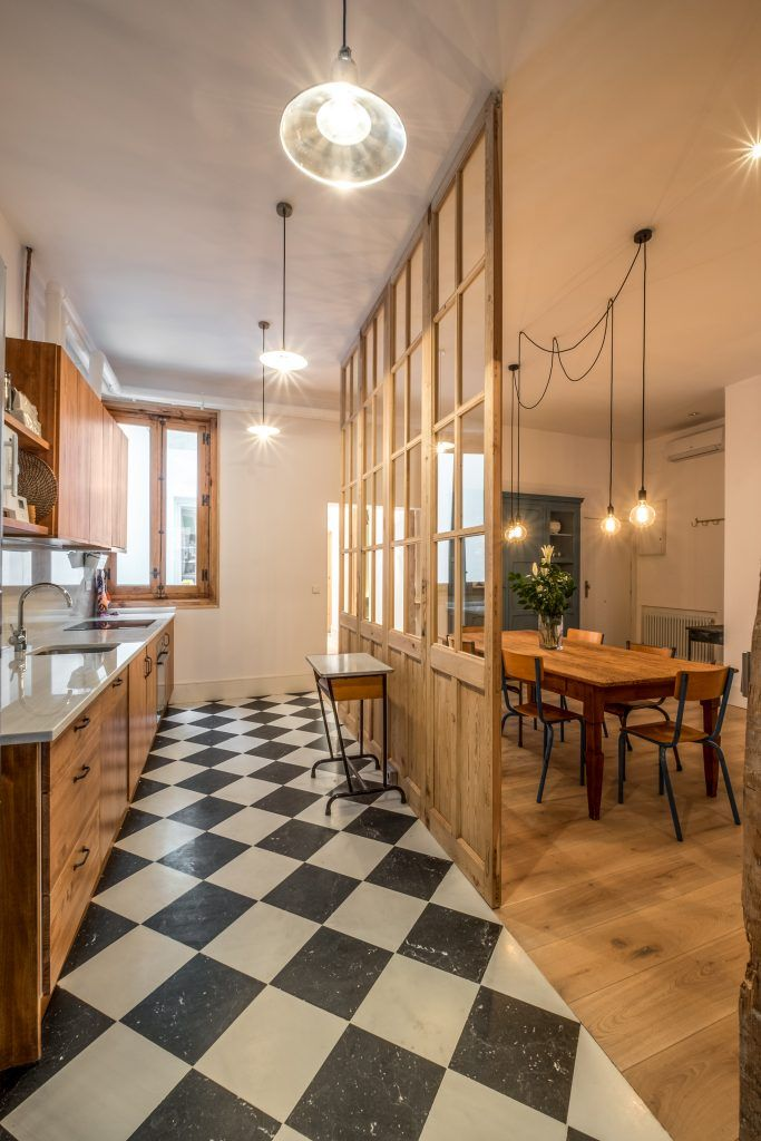 open room ,wooden floor, white black plaif floor, cream wall, pendants, wooden cabinet, white counter top, open shelves, wooden dining set