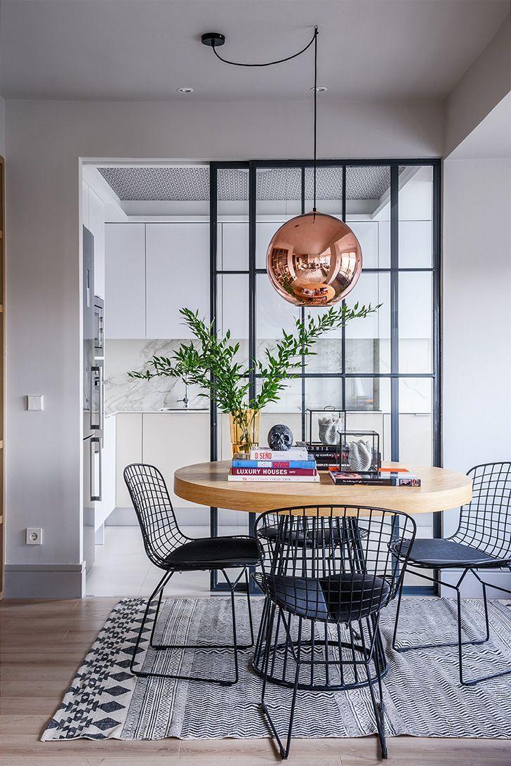 open room, wooden floor, white kitchen cabinet, white marble backsplash, white floor, copper pendant, round wooden table, black iron chairs