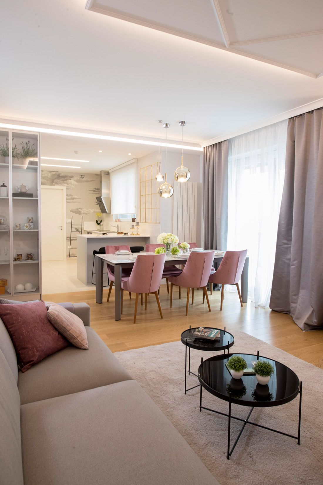 open space, wooden floor, brown rug, brown sofa, grey table, pink chairs, black tray coffee table