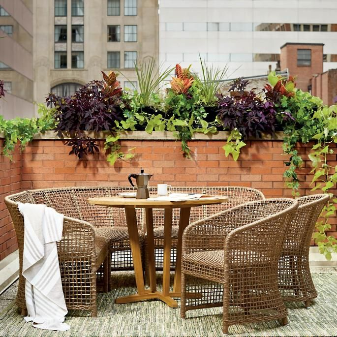 outdoor dining set, grey floor, exposed brick wall, rattan chairs, round wooden table