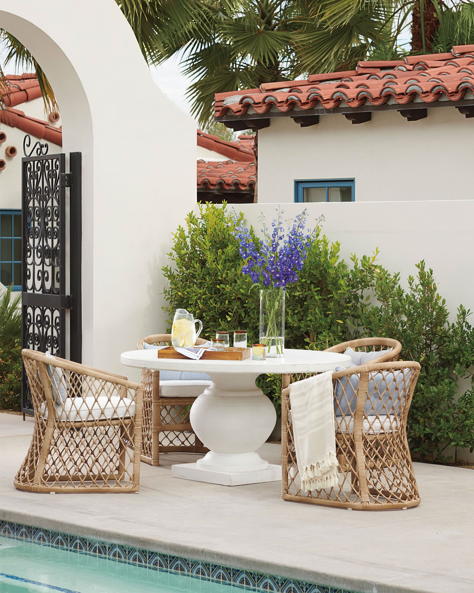 outdoor dining, white floor, white round table, rattan chairs with white cushion