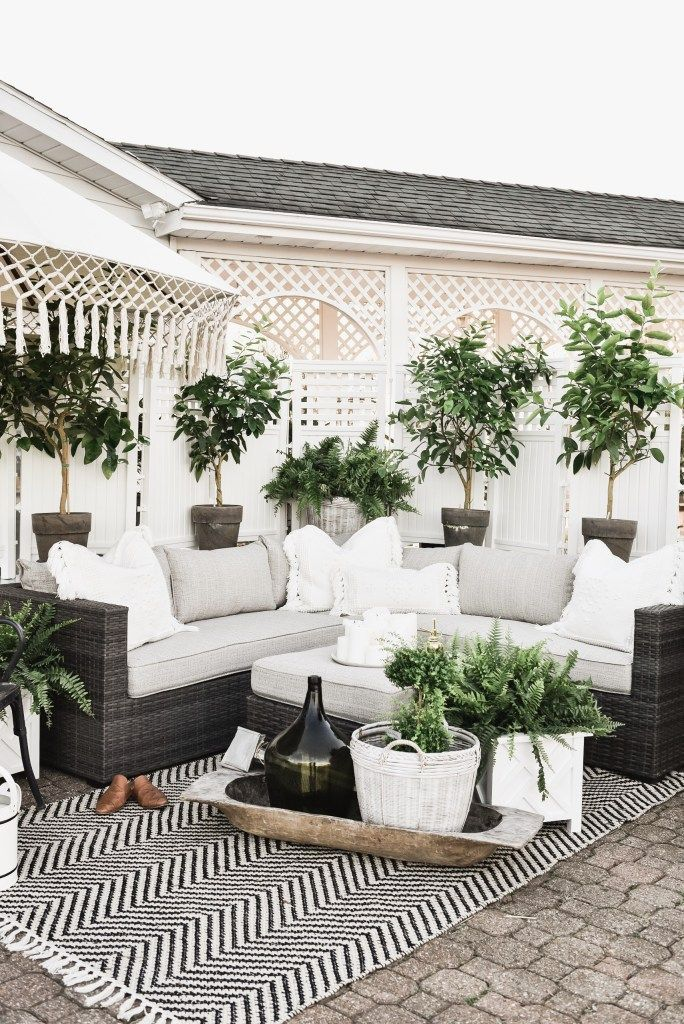 patio, concrete floor, white wooden screen, black rattan sofa and ottoman, white cushion, white pillows, black rug