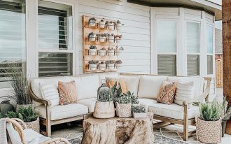 patio, light concrete floor, patterned floor, white wooden plank, light wooden sofa with white cushion, rattan chair, rattan pot, wooden coffee table