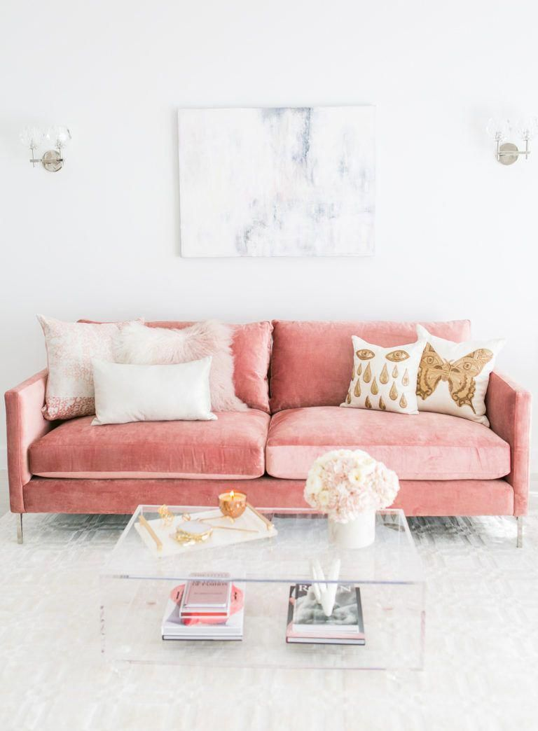 pink velvet sofa, white patterned floor, white wall, glass sconce, glass coffee table