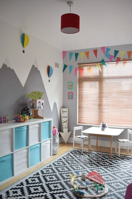 playroom, wooden floor, patterned rug, white blue shelves, white table and chairs