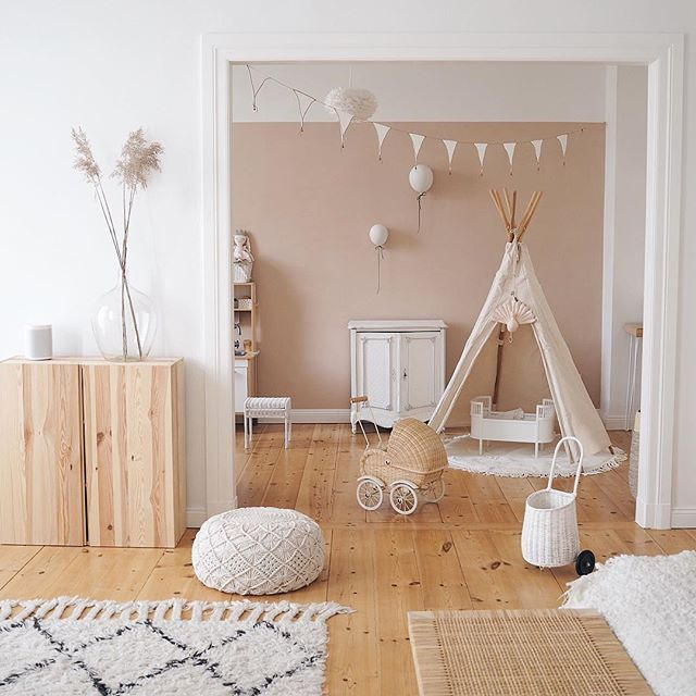 playroom, wooden floor, white wall, brown wall, wooden cabinet, white woven ottoman, white patterned rug, rattan rug, white wooden cabinet, white tent, rattan toys
