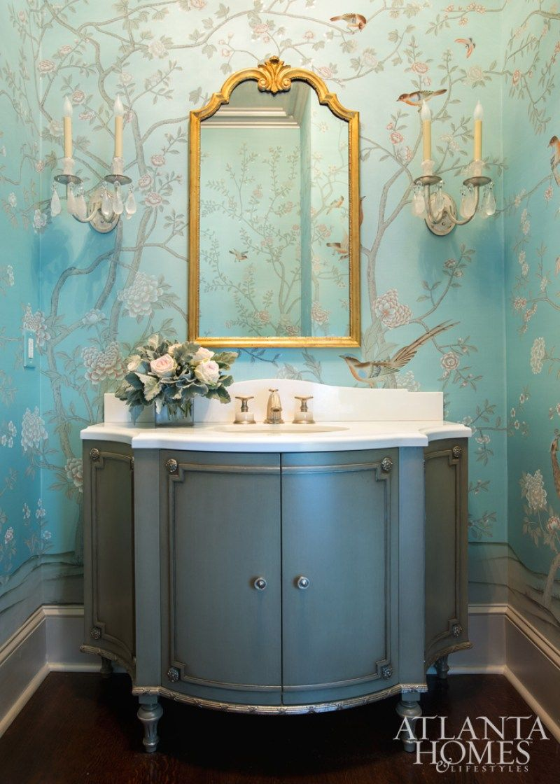 powder room, black floor, blue floewry wallpaper, blue cabinet with white top, classic sconces, golden framed mirror