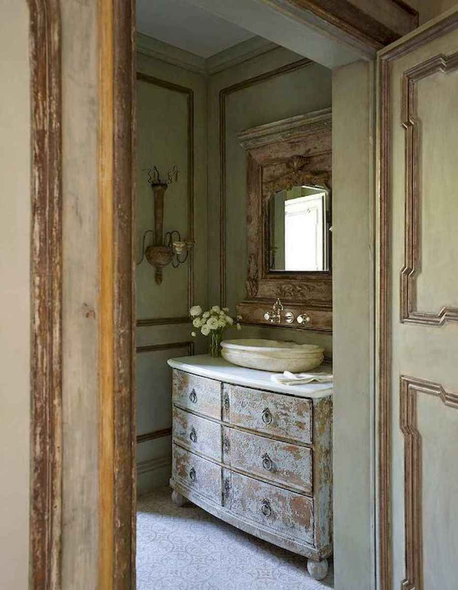 powder room, patterned floor, wooden wall, wooden vanity cabinet, white counter top, white oval sink, carved wooden framed mirror