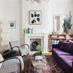 Purple Velvet Sofa, Colorful Rug, Wooden Floor, White Wall, White Fireplace, Grey Chairs