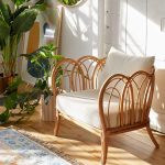 Rattan Chair With White Cushion, Wooden Floor, White Wall, Patterned Rug