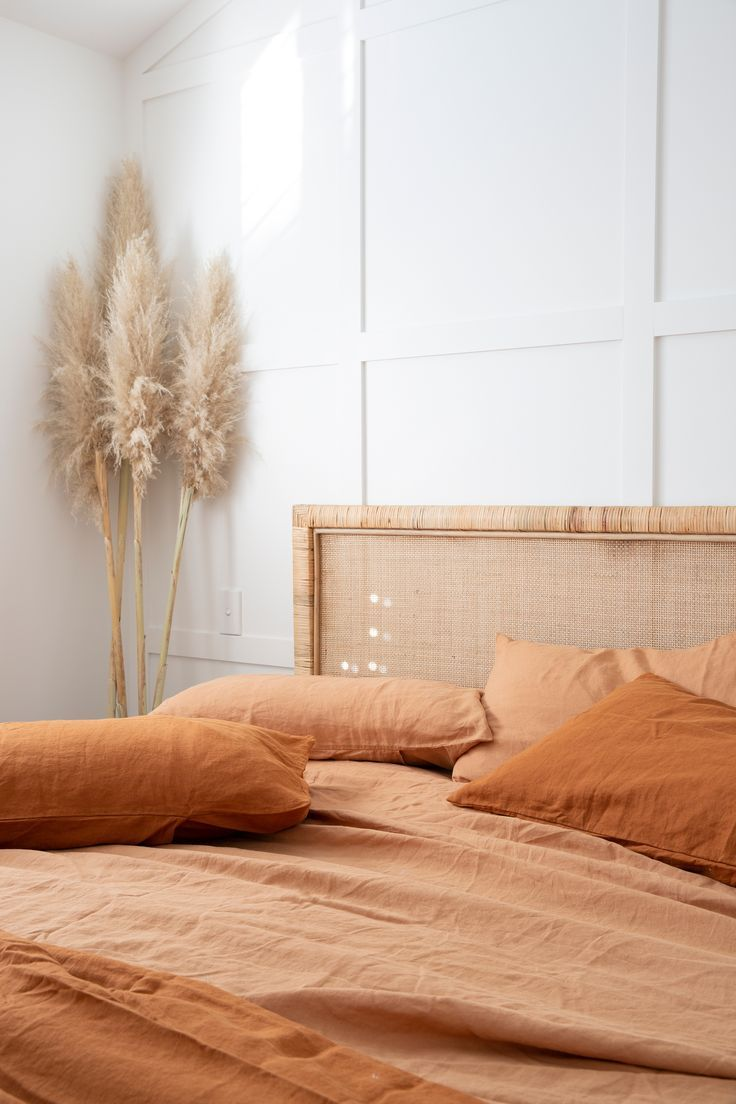 rattan headboard, white wall, orange bedding