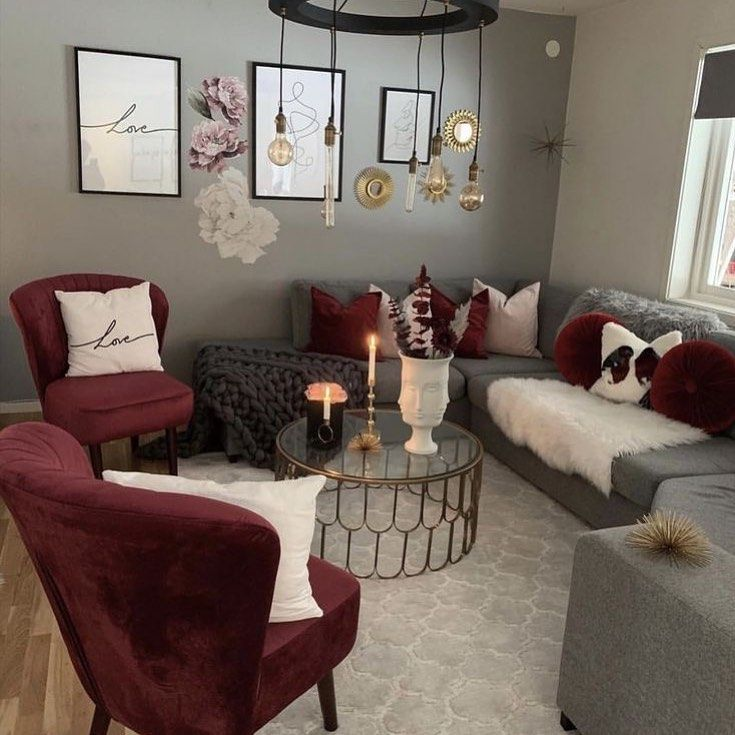 red velvet chair, grey sofa, round glass coffee table with golden lines, black chandelier