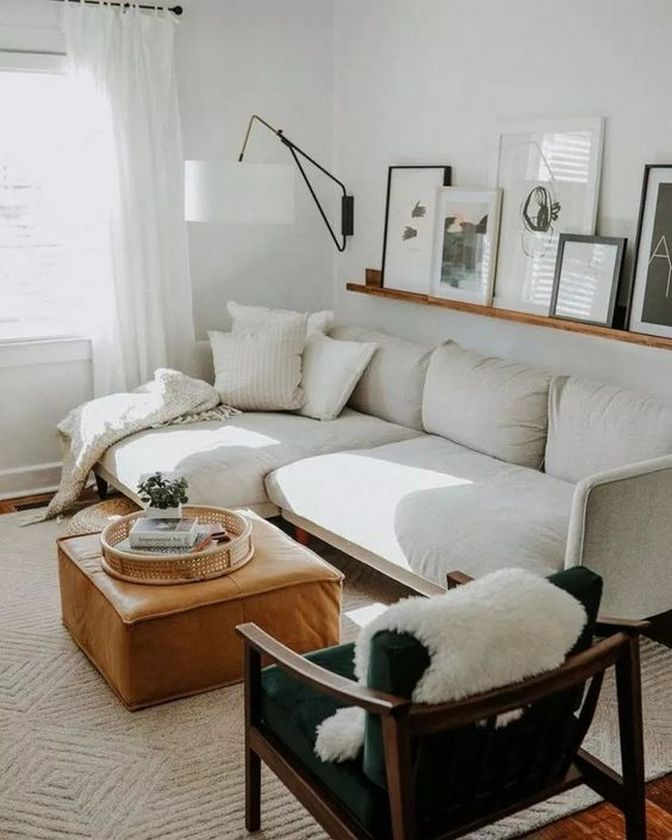 small living room, brown rug, white corner sofa, brown leather ottoman, dark chair, white wall, floating shelves, white sconce