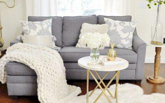 small living room, wooden floor, white wall, grey corner sofa, white round side table, wooden side table, white blanket