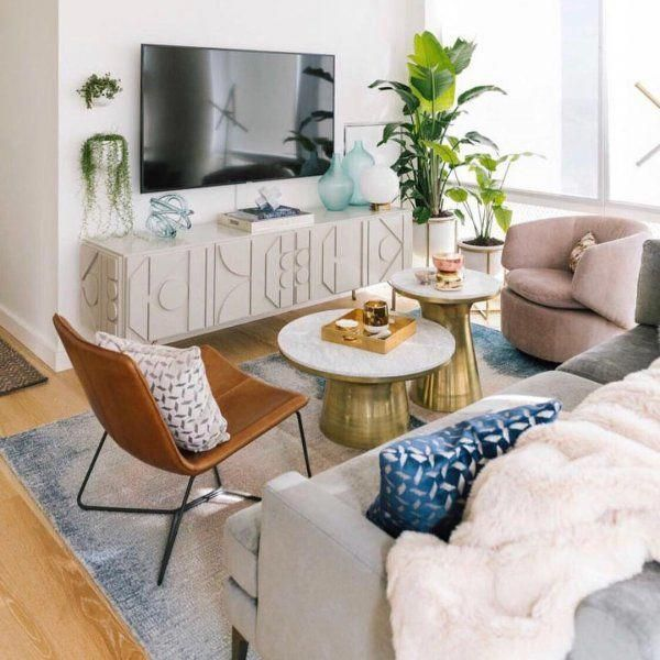 small living room, wooden floor, white wall, white cabinet, blue rug, pink chair, white round cofee table, grey sofa