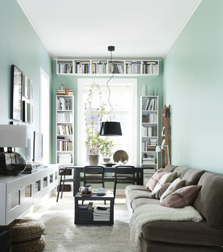 small living room, wooden floor, white wall, white floating cabinet, brown sofa, black coffee table, floating shelves, black table, black pendant, black chairs